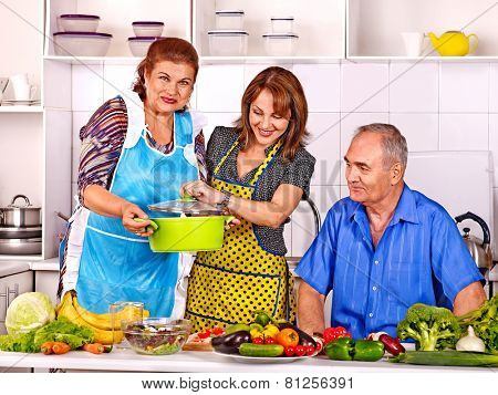 Big family cooking at kitchen. Grandfather and grandmother with his adult daughte