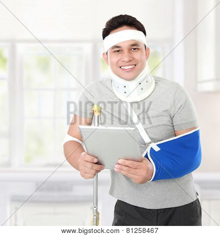 Injured Young Man Holding A Tablet