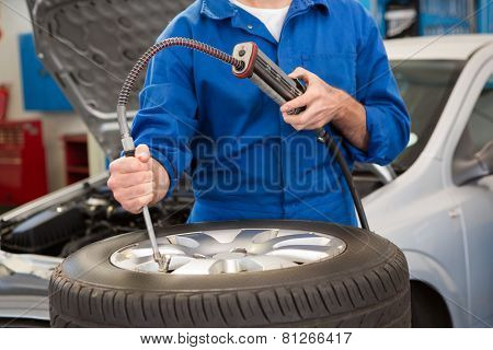 Close up of mechanic inflating the tire at the repair garage