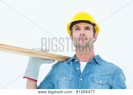 Handsome worker carrying wooden planks over white background