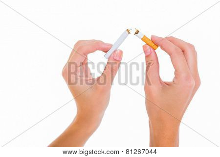 Womans hands snapping a cigarette on white background