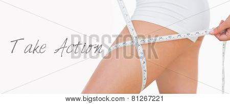 Midsection of woman measuring thigh over white background
