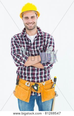 Portrait of happy male repairman wearing tool belt on white background
