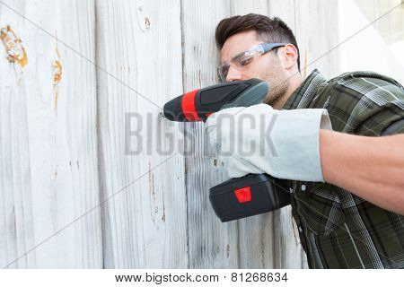 Male carpenter using hand drill on wooden cabin