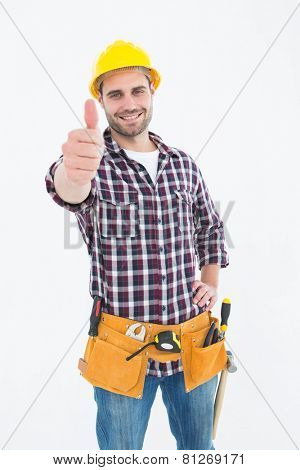 Portrait of male handyman gesturing thumbs up on white background