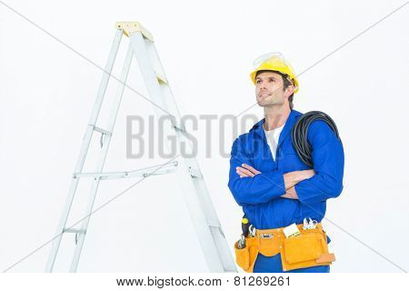 Thoughtful electrician with arms crossed standing by ladder over white background