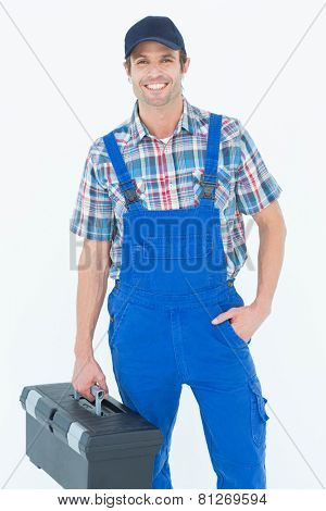 Portrait of confident plumber carrying tool box over white background