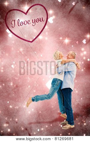 Mature couple hugging and having fun against valentines heart design
