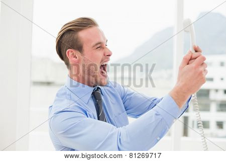Angry businessman screaming on the phone in his office