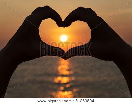 Heart Shape Making Of Hands Against Bright Sea Sunset