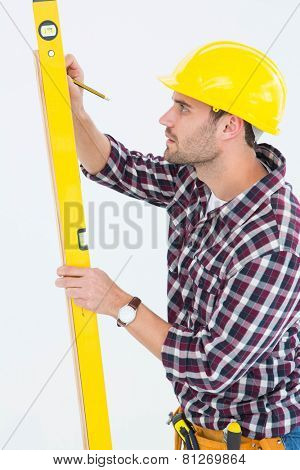Side view of technician marking while using spirit level on white background