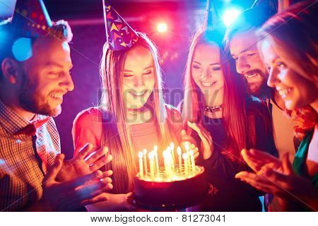 Pretty girl with birthday cake and her friends looking at burning candles at party
