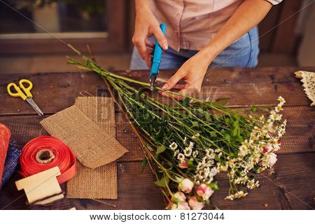 Female florist hands cutting floral stems at workplace