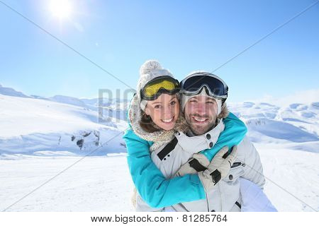 Man holding girlfriend on his back at the top of mountain