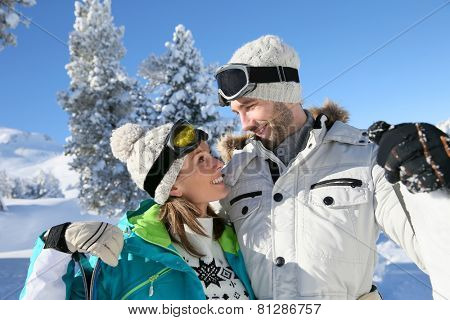 Cheerful couple of skiers looking at each other's eyes