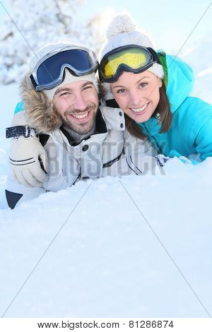 Portrait of loving couple of skiers in snowy moutain