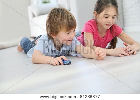 Kids playing with toy cars laying on floor
