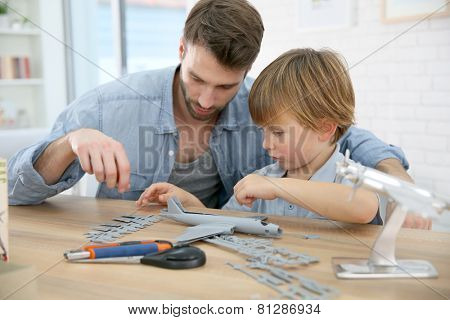 Father and son assembling airplane mock-up