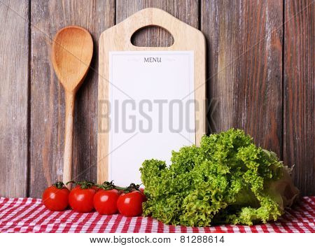 Cutting board with menu sheet of paper, with cherry tomatoes and lettuce on wooden planks background