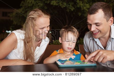 Family of three spending time in cafe with tablet computer