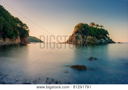 small rocky island while sunrise at ocean in italy