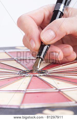 Female Hand Sticks Fountain Pen In The Target Center