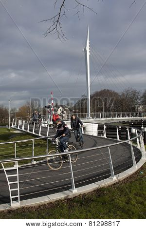 Cycling on the bridge, people crossing the river in rijswijk holland