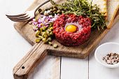 stock photo of tartar  - Beef tartare with capers and fresh onion on white wooden background - JPG
