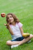 pic of  preteen girls  - Portrait of a preteen girl trowing apple in the air and with a pear in her other hand and green grass in the background - JPG