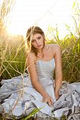 image of wearing dress  - An attractive young woman wearing formal attire is sitting in a grass field - JPG
