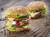 foto of hamburger-steak  - Two hamburgers on old wooden table - JPG