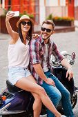 stock photo of love making  - Beautiful young loving couple sitting on scooter together and making selfie by their smart phone - JPG