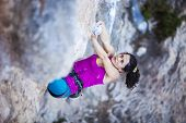 image of cliffs  - Young female rock climber on a cliff face - JPG