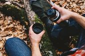 stock photo of thermos  - Unrecognizable traveler man pours tea or coffee from thermos in autumn forest - JPG