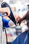 stock photo of hair blowing  - Female coiffeur blow dry women hair with blow dryer in shop - JPG
