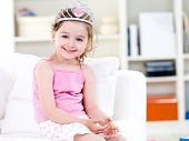stock photo of princess crown  - Beautiful little pretty princess in crown with attractive smile sitting on the sofa - JPG
