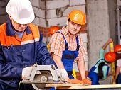 stock photo of millwright  - Happy group people  builder with circular saw - JPG