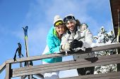 picture of log cabin  - Couple of skiers admiring panorama from log cabin - JPG
