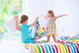 picture of pillow-fight  - Two children happy laughing boy and cute curly little girl having fun at pillow fight with feathers in the air jumping laughing and giggling in a white bedroom with colorful bedding - JPG