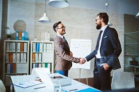 stock photo of joining  - Successful businessmen handshaking after negotiation - JPG