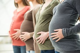 stock photo of life-support  - Side view of three pregnant women are touching their bellies with hands - JPG