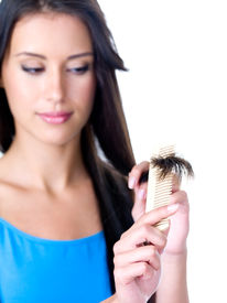 foto of split ends  - Beautiful brunette woman combing and looking on the ends of her long hair  - JPG