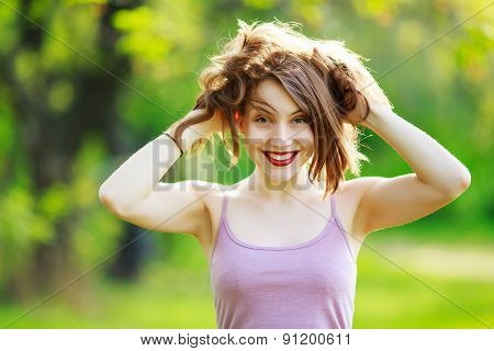 Portrait of a beautiful happy smiling girl with hand ruffled hair.
