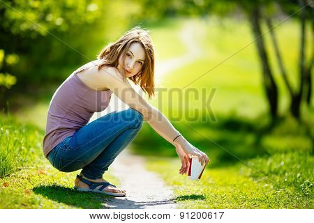 Young happy Caucasian blonde woman with coffee beverage sitting in park