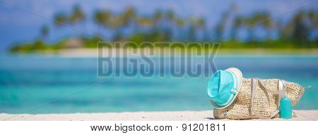 Straw bag, blue hat, sunglasses and sunscreen bottle on tropical beach