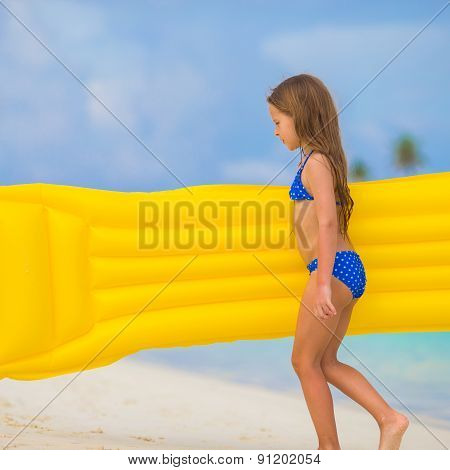 Adorable happy girl with inflatable air mattress on white beach