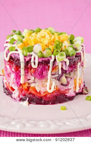 Traditional Russian Herring Salad On Pink Plate And Dark Pink Background