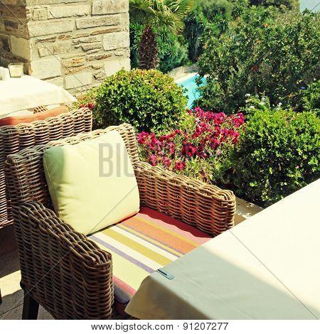 Wicker Armchair On Terrace Overlooking The Sea And Garden (Greece)