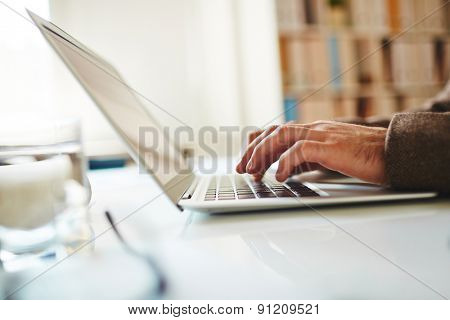 Hands of businessman typing on laptop