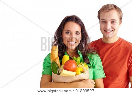 Happy girl holding sack with products and her boyfriend near by